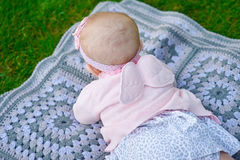 Happy little girl lying on a blanket in the park Royalty Free Stock Images