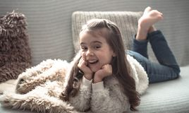 Happy little girl lying on the couch, beautiful smile royalty free stock photos