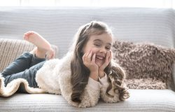 Happy little girl lying on the couch, beautiful smile stock image