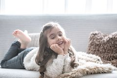 Happy little girl lying on the couch, beautiful smile stock images