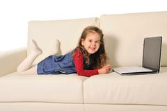 Happy little girl lying on couch playing with computer Royalty Free Stock Image