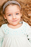 Happy little girl lying on floor. This image has attached release Stock Image