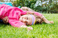 Happy little girl lying on grass stock images