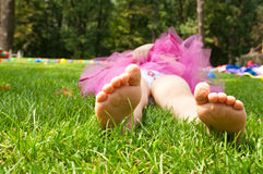 Happy little girl lying on green grass Royalty Free Stock Photo