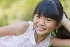 Happy little girl lying on the lawn Stock Photos
