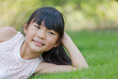 Happy little girl lying on the lawn Stock Images