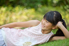Happy little girl lying on the lawn Stock Photography