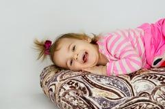 Happy little girl lying Stock Photo