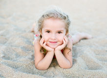 Happy little girl lying on the sand Stock Photos