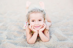 Happy little girl lying on the sand Stock Photo