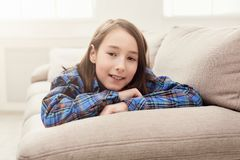 Happy little girl lying on sofa at home stock image