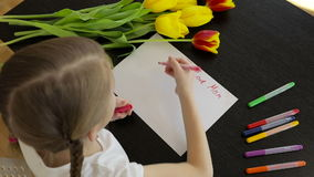 Happy little girl makes a holiday card for his mom on the table.