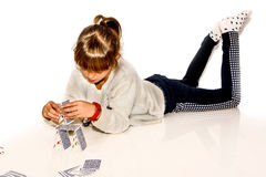 Happy little girl making house of cards isolated on white Royalty Free Stock Image