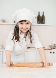 Happy little girl making pizza dough Royalty Free Stock Image