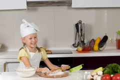 Happy little girl making pizza in the kitchen Stock Image