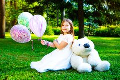 Happy little girl with many balloons and a teddy bear stock photos
