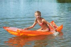 Happy little girl on mattress in lake Stock Photos