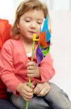 Happy little girl with mother holding pinwheel toy Royalty Free Stock Image