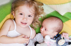 Happy little girl with a newborn brother Stock Photography