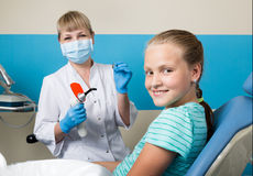 Happy little girl with open mouth undergoing dental treatment at clinic. Dentist checked and curing teeth a child. Patient in the dental office Royalty Free Stock Image