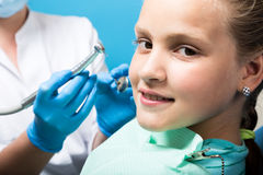 Happy little girl with open mouth undergoing dental treatment at clinic. Dentist checked and curing teeth a child Royalty Free Stock Photography