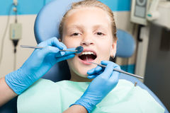 Happy little girl with open mouth undergoing dental treatment at clinic. Dentist checked and curing teeth a child. Patient in the dental office Stock Image