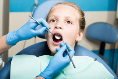 Happy little girl with open mouth undergoing dental treatment at clinic. Dentist checked and curing teeth a child. Patient in the dental office Royalty Free Stock Photography