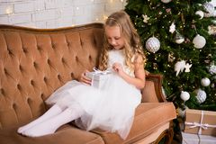 Happy little girl opening christmas gift in living room with Chr stock photo