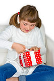Happy little girl opening a present. Sitting on a white couch Royalty Free Stock Photography
