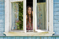 Happy little girl opens a window of rustic house in the early sunny morning Stock Photos