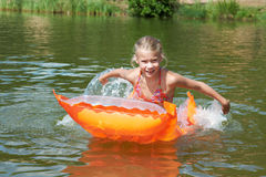Happy little girl on orange mattress in lake Stock Photos