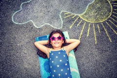 Happy little girl outdoors. Happy little girl wearing swimsuit and stylish sunglasses lying down on the asphalt near picture of the sun comes out from behind the stock images