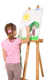 Happy little girl painting on easel Stock Photography