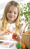 Happy little girl painting easter eggs Royalty Free Stock Image