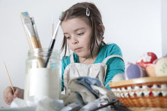 A happy little girl painting easter eggs Royalty Free Stock Images