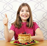 Little girl with panckaces dessert and thumb up Stock Photos