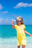 Happy little girl with paper airplane in hands on Stock Images