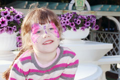 Happy little girl with pictured purple butterfly on face Stock Photography