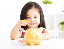 Happy little girl with  piggy bank Royalty Free Stock Photos