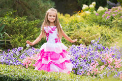 Happy little girl in a pink dress at flower bed Royalty Free Stock Image