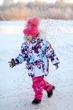 Happy little gir run with confetti. Happy little girl in pink hat run in confetti outside in white snow Stock Photography