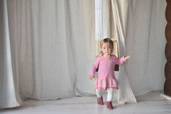 Happy little girl in pink indoors Stock Photo