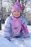 Happy little girl in pink scarf and hat crawls in snow Stock Photos