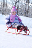 Happy little girl in pink scarf and hat goes tobogganing Royalty Free Stock Photography