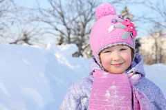 Happy little girl in pink scarf and hat looks at camera Stock Photo