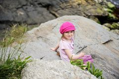 Happy little girl in pink sun hat on the rocks Stock Images