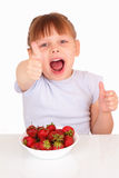 Happy little girl with plate with strawberries Stock Photo