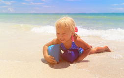 Happy little girl play with armbands at sea. Swimming safety Stock Photos