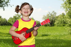 Happy little girl play guitar Royalty Free Stock Images