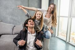Happy little girl play with her mother and father. On the sofa stock photo